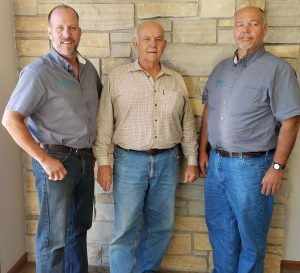 Three men smiling together for a photo